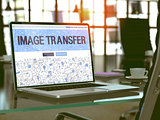Image Transfer on Laptop in Modern Workplace Background.