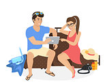 Young couple sitting on the luggage and using tablet pc to watch photos from their holiday