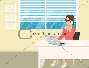 Business woman wearing rose shirt sitting in the office and talking by cellphone