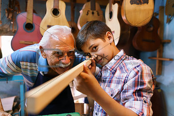 Old Man Luter Teaching Grandson Boy Chiseling Wood