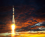 Carrier Rocket On A Background Of Red Clouds