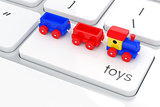 Wooden colorful train toy on the computer keyboard. Play games c