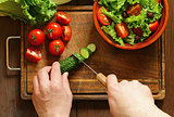 cooking vegetable salad (tomatoes, lettuce, cucumbers) on a wooden board, top view
