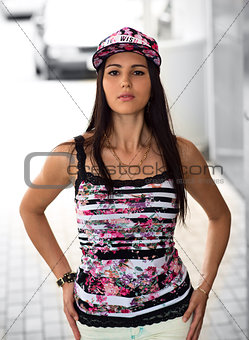 Beautiful girl in a cap, fashion style youth posing the city