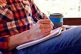 young man writing in a notebook