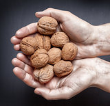 hands holding handful of walnuts