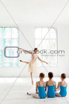 Three little ballerinas dancing with personal ballet teacher in dance studio
