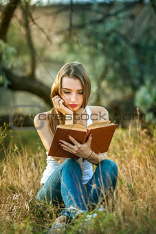 Beautiful girl reading a book on the Nature