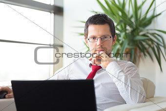Portrait of businessman working on laptop computer