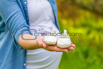 close up of pregnant woman hand with baby shoes