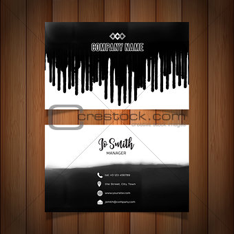 Business card with black paint drips