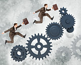 Two businessmen running on wheel gears