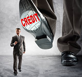 Big foot steps on businessman
