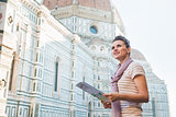 Happy woman with tourist map looking into distance in Florence