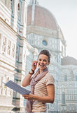 Happy woman tourist with map having audio walking tour, Florence