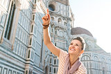 Smiling woman tourist pointing on something near Duomo, Florence