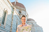Happy woman tourist looking at map while standing near Duomo
