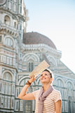 Smiling woman tourist with map sightseeing in Florence, Italy