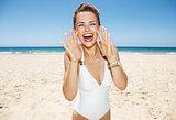 Woman shouting through megaphone shaped hands at sandy beach