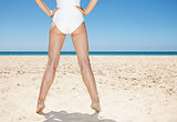 Closeup on legs of woman in white swimsuit at sandy beach