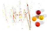 Gouache jars and paint brushes on a white background with colorful spray in top view