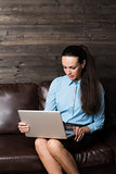 Happy brunette sitting on sofa in living room using laptop