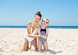 Happy mother and child at beach showing hands full of sand