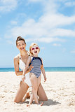 Smiling mother and child in swimsuits at beach on a sunny day