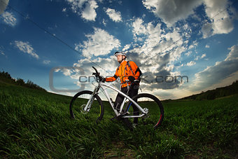 Cyclist with  the Bike on meadow