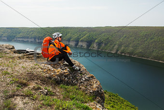 Cyclist in Orange Wear Sitting on Rocky Hill