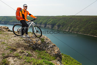 Cyclist in Orange Wear Riding the Bike Down Rocky Hill