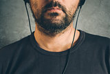 Man listening to music on headphones, half face portrait