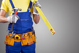 construction worker with tool belt on gray with copy space