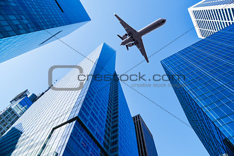 airplane over skyscrapers