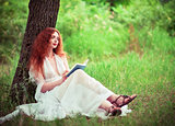 Beautiful ginger woman sitting under tree and reading a book