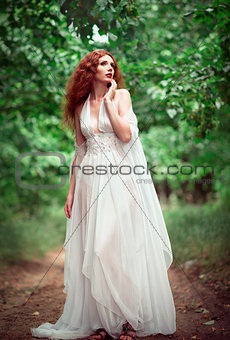 Beautiful ginger woman wearing white dress in a grove