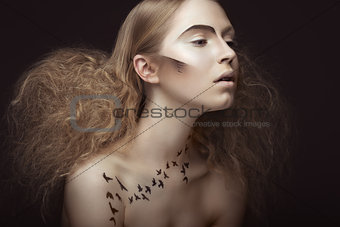 Beautiful girl with a pattern on the body in form of birds, creative makeup and hairstyle lush. Beauty face.