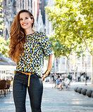 Smiling woman tourist near Sagrada Familia having walking tour