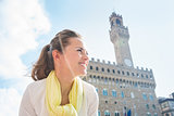 Smiling woman standing near Palazzo Vecchio and looking aside