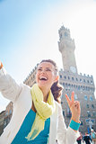 Woman showing victory and taking selfie near Palazzo Vecchio