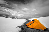 Orange tent in snow mountains. Selective color.