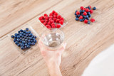 Closeup on man with a glass of water healthy berries on table