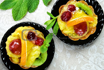 Cakes with slices of fresh fruit.