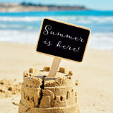 text summer is here in a signboard topping a sandcastle