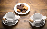 Set of two ceramic tea mugs with sachet and plates of cookies. Preparation for brewing tea.