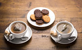 Set of two ceramic tea mugs with sachet and plates of cookies.
