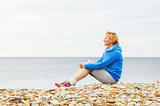 Woman sitting on the beach and looks into the distance