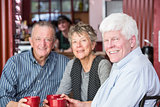 Mature Man with Friends in Coffee House