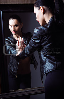 Portrait of beautiful young woman looking into the mirror