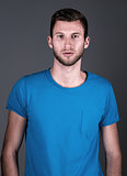 Studio fashion shot: portrait of handsome young man in blue shirt